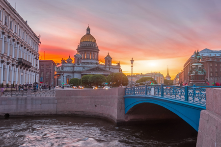 St. Isaac's Cathedral in the square, in St. Peterburg in the evening on a bright orange sunset sky, by the embankment of the Moika River and the blue bridge