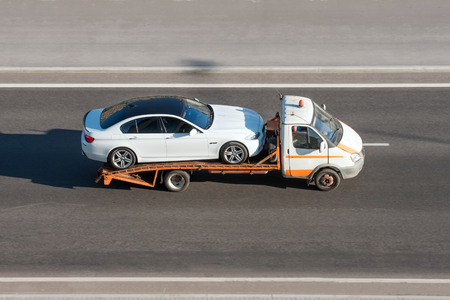 Car is transported on an evacuation tow truck on the highway Stock Photo