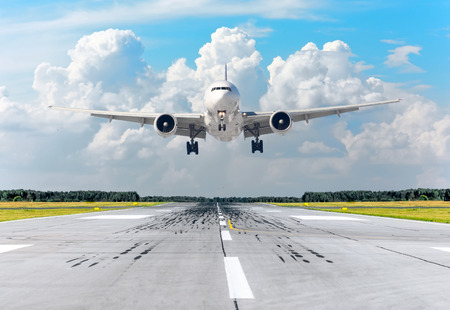 Passenger airplane landing at in clouds sky on a runway