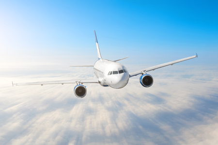 Airplane in the sky above the clouds flight journey sun height speed motion blur. Passenger commercial aircraft. Business travel. Aerial