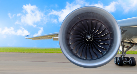 Aircraft jet engine close-up, airplane wing and chassis of landing gear wheel parked at the airport on a sky clouds background, panorama