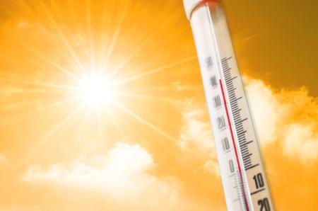 Thermometer gegen den Hintergrund eines orangegelben heißen Glühens der Wolken und der Sonne, Konzept des heißen Wetters Standard-Bild