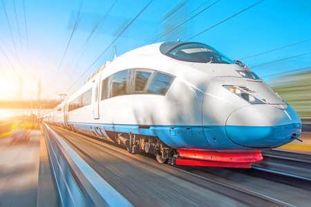Il treno ad alta velocità viaggia ad alta velocità alla stazione ferroviaria della città Archivio Fotografico