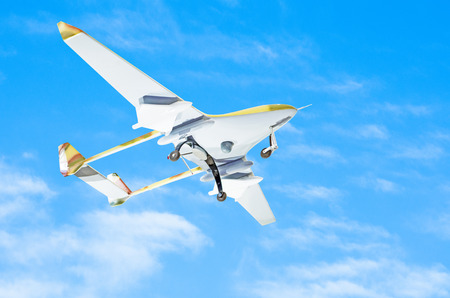 Unmanned aerial vessel is gaining altitude to track a mission against a blue sky Stock Photo