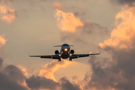 Dark silhouette of an small airplane at sunset approach in the airport of a beautiful beautiful sky