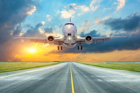 Passenger airplane landing at sunset on a runway Stok Fotoğraf