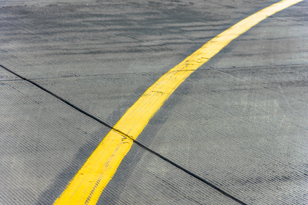 Yellow direction strip fork close up on an airfield runway