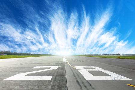Landingsbaan van de luchthaven tot in de horizon en pittoreske cirruswolken in de blauwe lucht