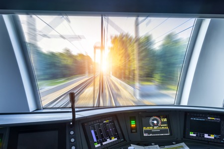 Driver's cab of speed passenger train, view of the railway bridge with the effect of speed motion blur