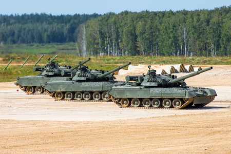 Three military tanks stand on the field with muzzles raised in the sky