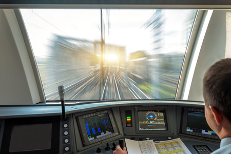Train driver at the controls cab of speed passenger train, view of the railway bridge with the effect of speed motion blur Archivio Fotografico