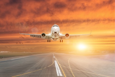 Passenger airplane landing at sunset on a runway 写真素材