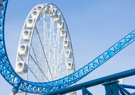 Ferris wheel and Loop turn on a blue roller coaster in an amusement park
