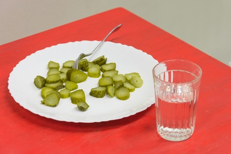 Chopped pieces of pickled cucumbers on a red table in a plate with a fork and a glass of vodka Reklamní fotografie