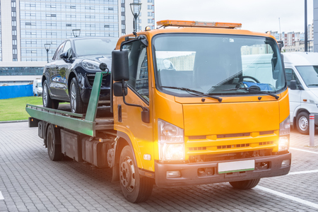 Passenger car loaded onto a recovery truck for transportation Stock Photo