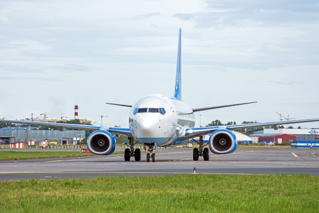 Passenger aircraft taxiing on the apron of the airport on the asphalt is visible marking Stock Photo