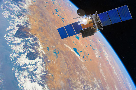 Low-orbit communication satellite in space above the Earth. Elements of this image furnished Imagens - 112268106