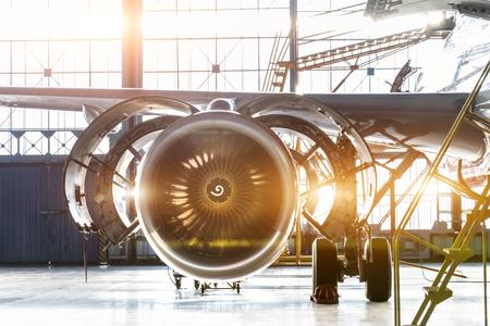 Odrzutowiec silnika samolotu z otwartą maską w trakcie konserwacji w hangarze, z jasną flarą światła przy bramie