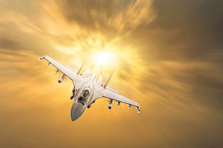 Furious military fighter jet with fire from engines flies in the orange sunset sky Reklamní fotografie