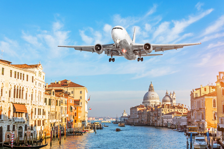 View on Grand canal and airplane flying in the sky. Italy travel concept.