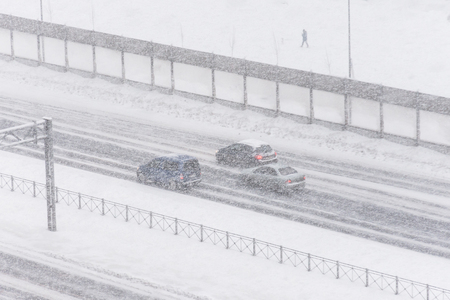Cars in the snow are driving on the highway, with poor visibility.