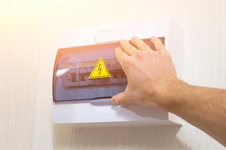 Hand ist ein offenes elektrisches Phasenblitzzeichen, wurde an der Wand installiert. Standard-Bild