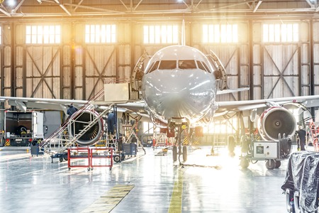 Passenger aircraft on maintenance of engine repair in airport hangar Stock Photo
