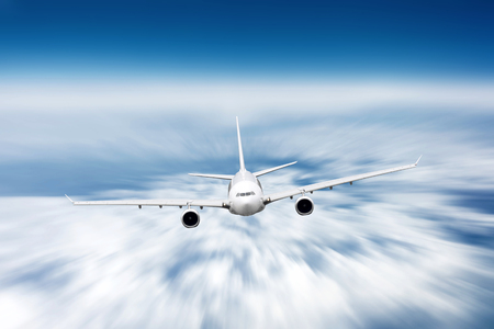 Modern airplane mith motion blur effect travel at sunny bright day.