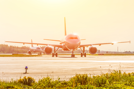 Two passenger aircraft on taxi to the terminal after landing, bright sunlight on the background
