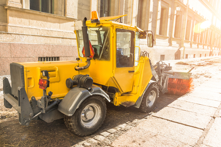 Yellow urban sweeper cleans road embankment dirt with a round brush Foto de archivo