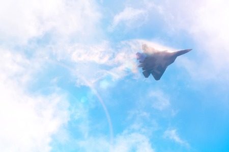 One military fighter aircraft at high speed, flying high clouds in the sky, sunshine glare