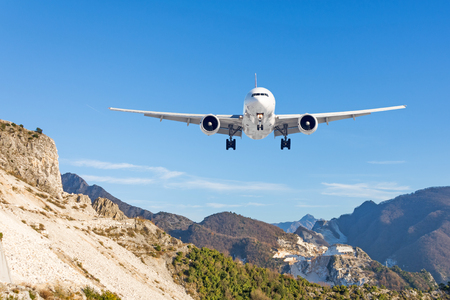 Mountain landscape and landing passenger aircraft. Travel to the mountainous countries. Stock Photo