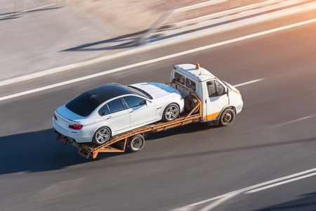 Recovery truck to transport a car on the highway in the city. Stockfoto