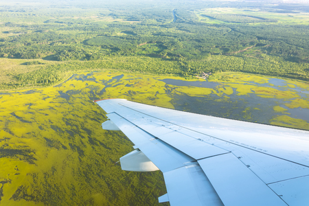 View from window airplane to forests, fields, lakes, swamps 写真素材