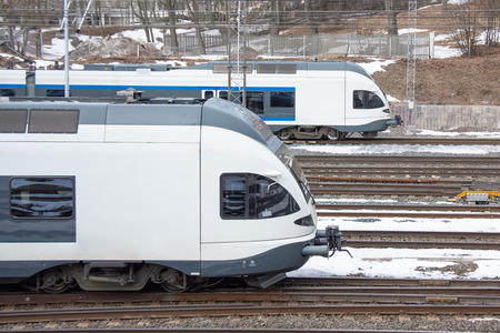 Commuter trains overtake each other on the railroad.