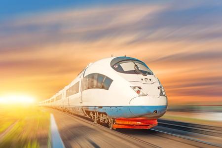 Locomotive high speed train runs on rail track, sunset sky