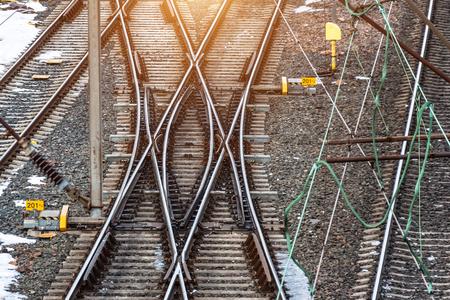 Paesaggio industriale con binari ferroviari su traversine ferroviarie in cemento, frecce Archivio Fotografico
