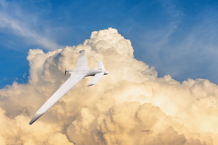 Patrolling unmanned aircraft in the sky against the backdrop of powerful thunderstorm clouds