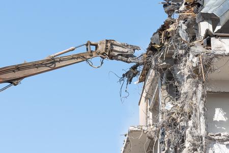 Heavy equipment hydraulic shears arrow dismantle the building, demolition destruction