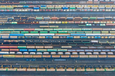 Aerial view of railroad tracks, cargo sorting station. Many different railway cars with cargo and raw materials