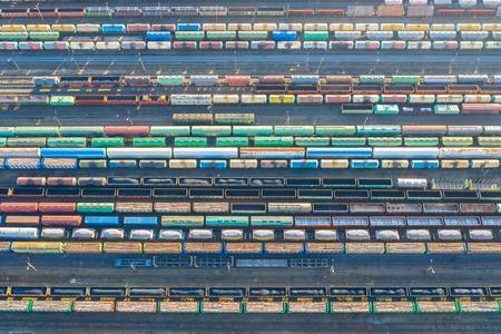 Luftaufnahme von Bahngleisen, Frachtsortierstation. Viele verschiedene Eisenbahnwaggons mit Fracht und Rohstoffen