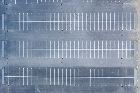 Top aerial view of parking to a large area empty asphalt car parking