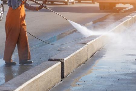 Trabajador de limpieza de entrada con lavadora de alta presión de gasolina salpicando la suciedad, borde de la carretera de asfalto. Limpieza a alta presión