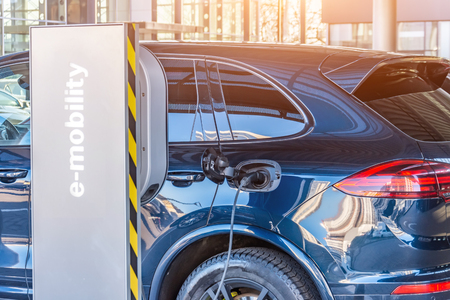 Charging the machine, compartment door is open, the electric plug under voltage restores the battery charge. Refueling for electric cars e-mobility Banco de Imagens