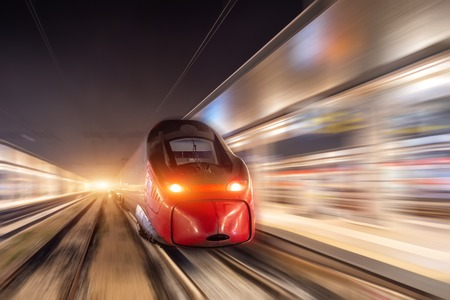 Night passenger high-speed train passing the station in the city Stockfoto