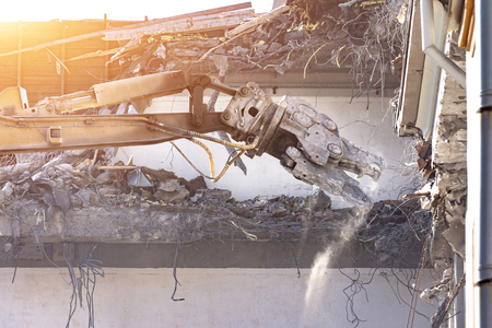 Heavy equipment hydraulic shears arrow dismantle the building, demolition destruction. Close up view