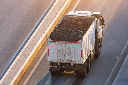 LKW, der hinten mit Erde beladen ist, steht am Straßenrand Standard-Bild