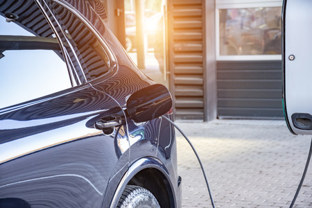 Carga de un coche eléctrico en un taller de reparación de automóviles. Reabastecimiento de combustible para coches eléctricos e-movilidad