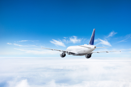Samolot leci nad chmurami wysoko na niebie Zdjęcie Seryjne