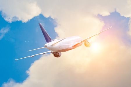 Travel to faraway countries. The plane flies gaining altitude in the clouds to the bright sun